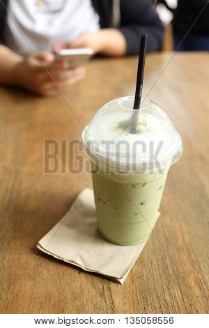 Cool green tea on wooden desk with coffee cafe background