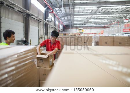 Gu'an, China - June 14, 2016: JD.com staff receiving incoming goods, sorting products, and preparing shipments at the Northeast China based Gu'an warehouse and distribution facility