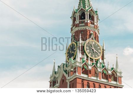 Kremlin tower of red brick, with a big clock on a sky background