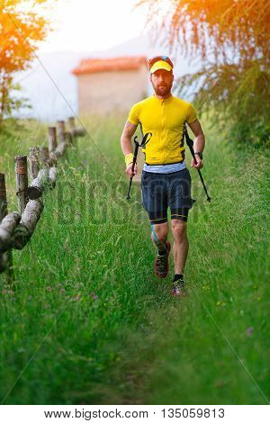 Nordic Walking In The Grass With Sticks In Hand