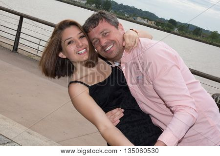 Man And Woman On The River Bank Embraces, Happiness