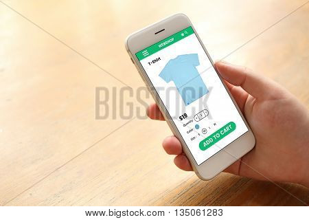 Hand holding smartphone with ecommerce screen website