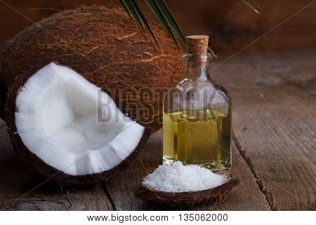 Coconut oil , shells and flakes on old wooden background, selective focus.