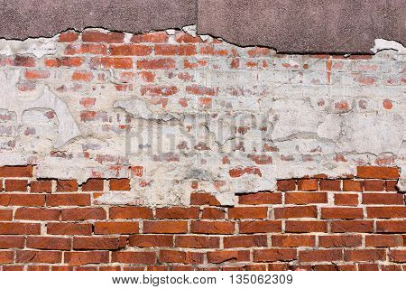 ancient texture of an old red brick wall with destroyed plaster for background in vintage style and for old wallpaper