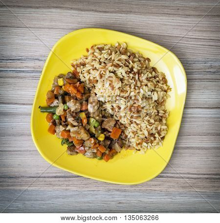 Chicken meat with fried rice and steamed vegetables. Serving food. Food theme. International cuisine. Close up. Lunch menu. One portion.