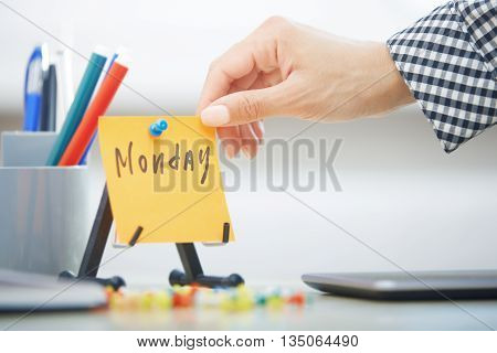 Human hand holding adhesive note with Monday text