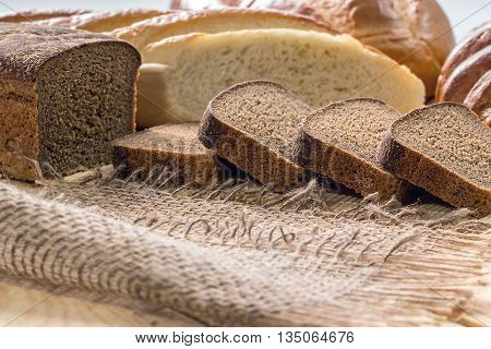Rye bread and white long loaf on an old wooden table