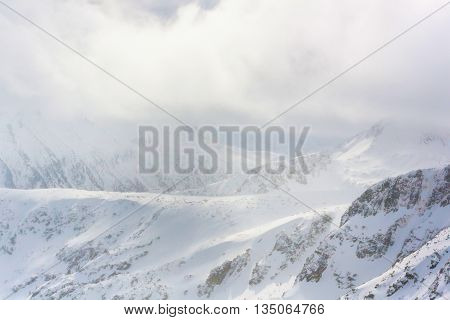 Panorama of white snow mountain landscape with fog and clouds