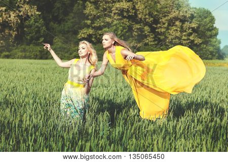 Woman walks across the field behind her levitating another woman.