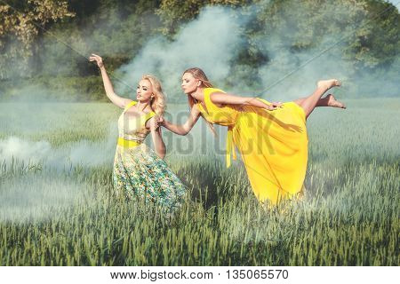 Over a field of white smoke. Woman flying over the field the second woman is holding her hand.