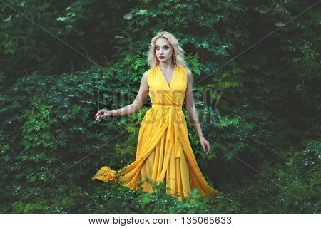 Charming blonde woman dressed in a yellow dress she stands among the green bushes in the forest.