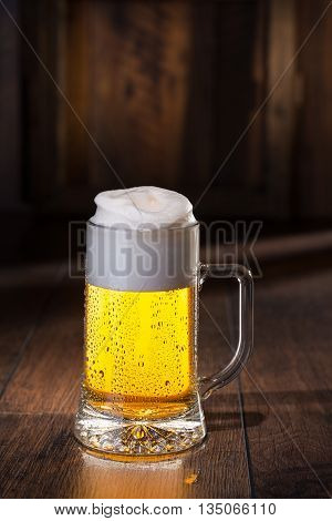 Frosty glass of beer and wood on background