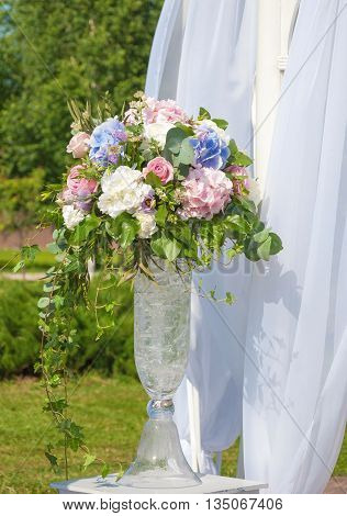 Beautiful bouquet of roses and hydrangeas on a background of light curtains
