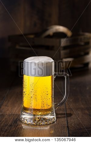 Frosty glass of beer and bottles on background