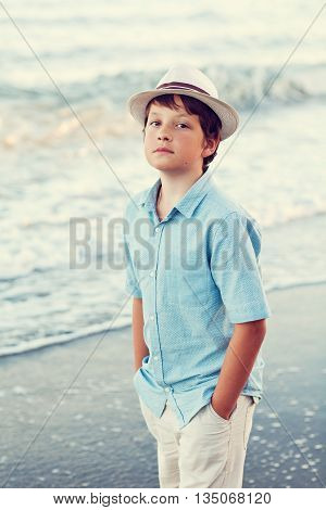 portrait of a cute boy on the beach on a summer day .