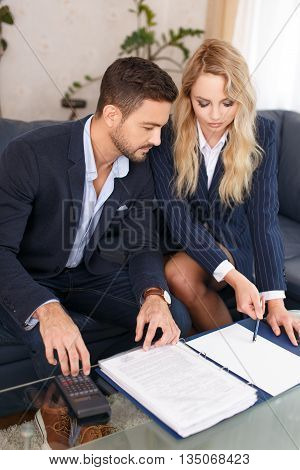 Young CEO with blonde assistant review financial results in office