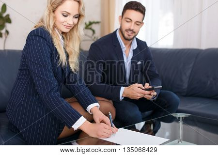 Business woman and businessman calculate on glass desk
