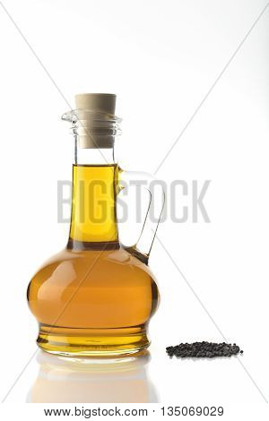 High resolution image of mustard oil decanter with mustard seeds shot in studio on white background