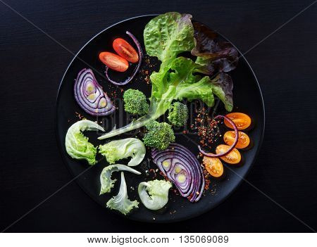 Fresh salad with cherry tomatoes lettuce red onion and broccoli on a black plate and flat black wooden table. Low key