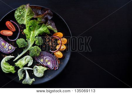 Fresh salad with cherry tomatoes lettuce red onion and broccoli on a black plate and flat black wooden table. With place for your text. Low key