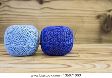 Blue balls of cotton yarn for knitting, crochet on bamboo background