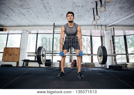 Muscular young fitness man workout with barbell in fitness gym