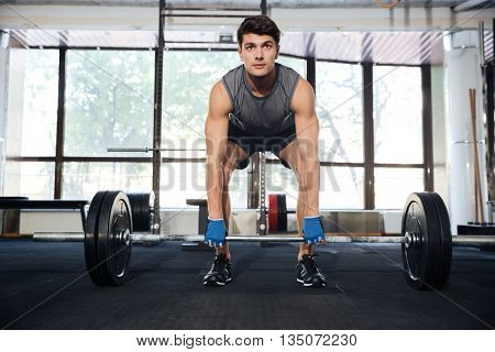 Handsome man workout with heavy barbell in gym