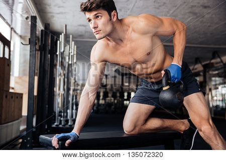 Handsome fitness man lifting kettle ball on the bench at the gym
