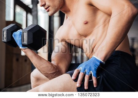 Cropped image of a male bodybuilder workout with dumbbell in gym