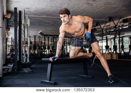 Handsome bodybuilder man workout with kettle ball on the bench at gym