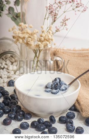 Juicy and fresh blueberries on the spoon with yogurt. Bilberry on the white table background. Blueberry antioxidant. Concept for healthy eating and nutrition.