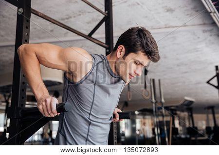 Portrait of a handsome fitness man doing exercise on parallel bars in fitness gym