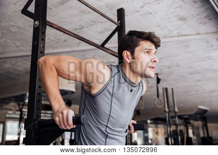 Portrait of a handsome young man doing exercise on parallel bars in fitness gym