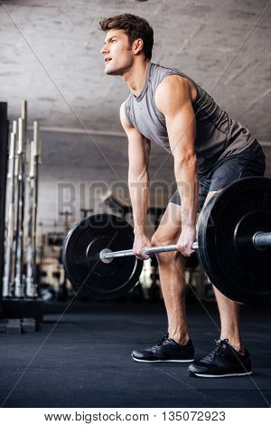 Muscular handsome man workout with barbell in fitness gym