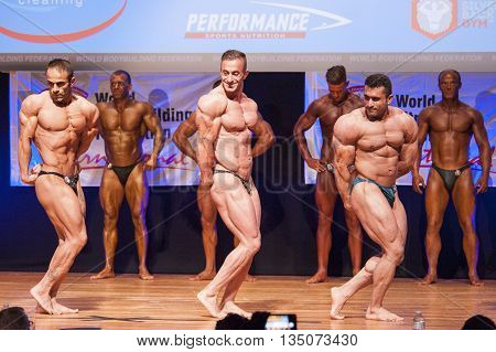 MAASTRICHT THE NETHERLANDS - OCTOBER 25 2015: Male bodybuilders flex their muscles and shows their best triceps pose on stage at the World Grandprix Bodybuilding and Fitness of the WBBF-WFF