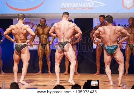MAASTRICHT THE NETHERLANDS - OCTOBER 25 2015: Male bodybuilders flex their muscles and shows their best lats spread pose on stage at the World Grandprix Bodybuilding and Fitness of the WBBF-WFF
