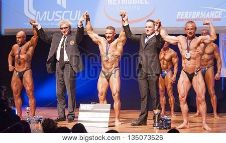 MAASTRICHT THE NETHERLANDS - OCTOBER 25 2015: Male bodybuilders celebrate their victory on stage with official at the World Grandprix Bodybuilding and Fitness of the WBBF-WFF