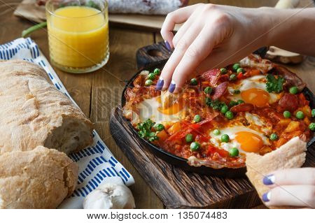 Hand of the girl dip bread into eggs a la flamenca. Spanish cuisine.