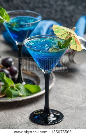 Blue cocktail with ice and mint in martini glasses on gray background