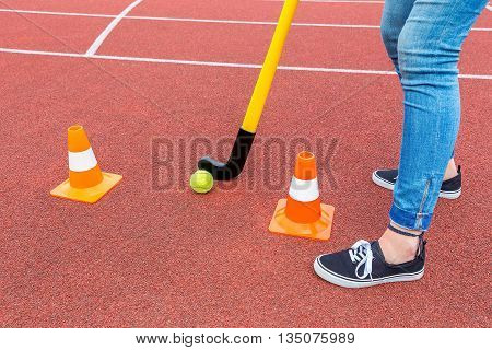 Legs of teenage girl as hockey player with stick ball and orange pawns