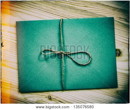 envelope tied with a rope wooden table