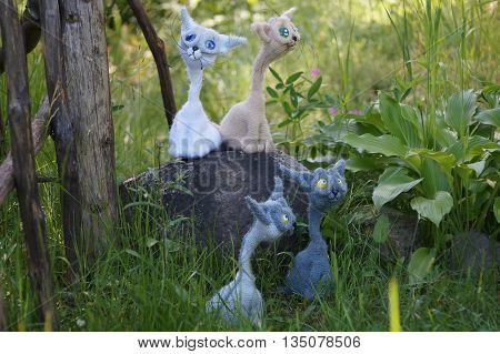 a flock of knitted cats walking in the green grass.