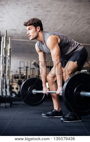 Muscular fitness handsome man workout with barbell in fitness gym