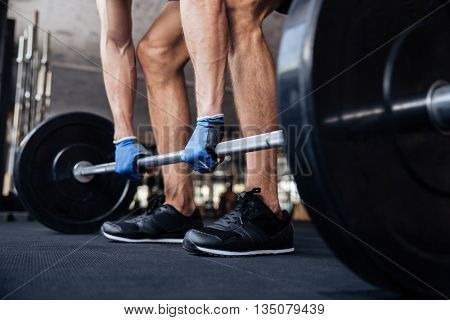 Cropped image of a muscular fitness bodybuilder man lifting heavy barbell in gym