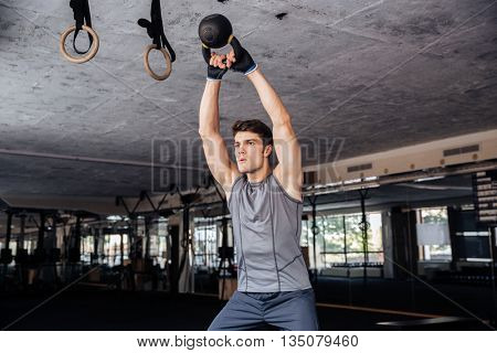 Young handsome bodybuilder using kettlebell in his workout at the gym