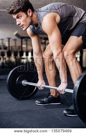 Muscular young handsomoe man workout with barbell in fitness gym