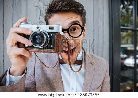 Happy funny stylish nerd holding camera outdoors