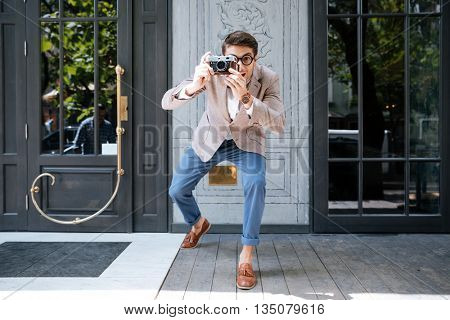 Cheerful funny man in round glasses standing and taking pictures on the street of the city