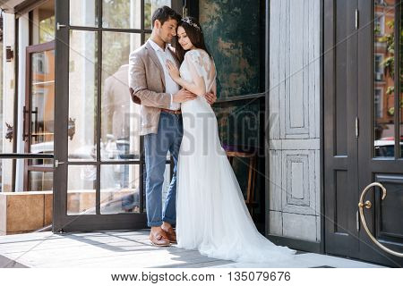 Full length portrait of modern tender young couple of groom and bride