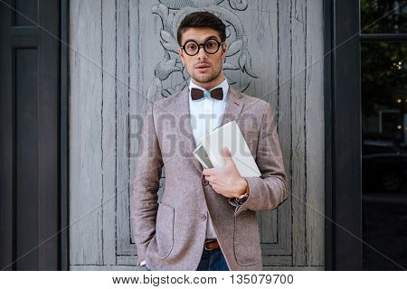 Young fashion man with nerd glasses and stylish hairdo in jacket posing